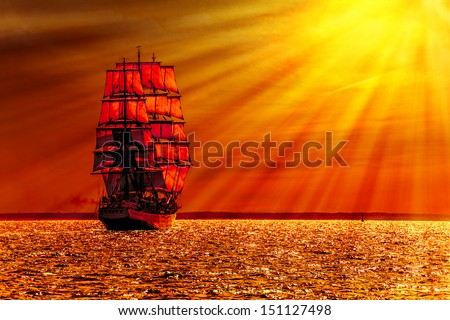 Sailing ship on the sea at sunset skyline.