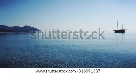Sailing ship profile. Toned image. Sunbeams on the sea surface. Morning sea with boat on the horizon. Aged photo. Calm Sea with a Sailing Vessel. Cirali, Antalya Province, Turkey.