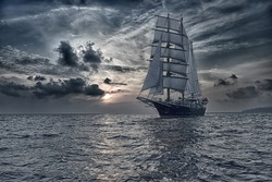 Sailing ship under white sails and stormy sunset sky. Yachting. Travel