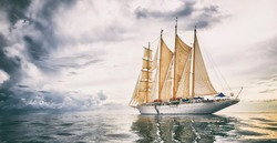 Sailing ship with sails against the background of the storm sky. Yachting. Cruise. Sailing