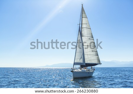 Sailing ship yachts with white sails in the open Sea. Luxury boats.