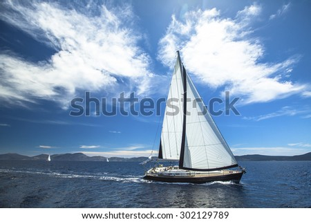 Sailing ship yachts with white sails in the open Sea. Luxury lifestyle.