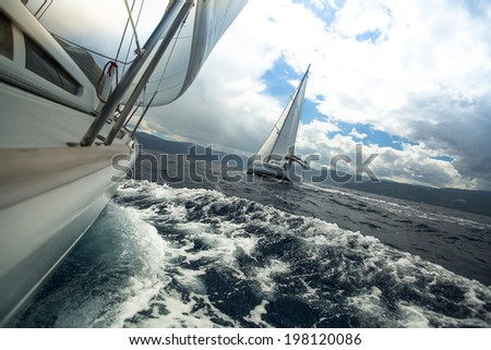 Sailing ship yachts with white sails in the sea in stormy weather