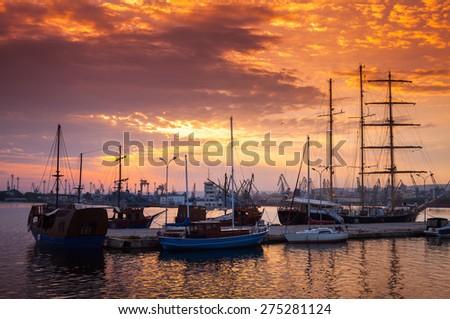 Sailing ships and yachts stand moored in Varna harbor at the sunset. Black Sea coast, Bulgaria