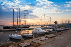 Sailing ships and yachts stand moored in Varna port at the sunset. Black Sea coast, Bulgaria