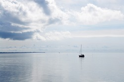 Sailing small boat yacht alone lonely on calm baltic sea clouds seascape
