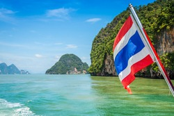 Sailing to Phi Phi island, a famous travel destination in the Andaman sea in south Thailand. The flag is Thailand national flag.