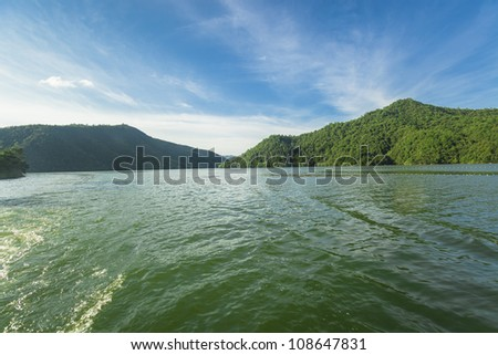 Sailing toward to an island in a big lake under blue sky with clouds