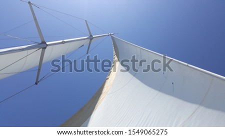 Sailing under the blue sky on a sunny day. Sails of a sailing yacht in the wind. Close up of yacht mast and sail on sky background. Sailing boat part.