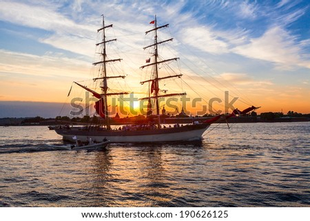 Sailing vessel on the background of the Peter and Paul fortress in the rays of the setting sun
