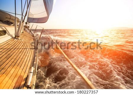Sailing yacht against sunset. Luxury yachts.