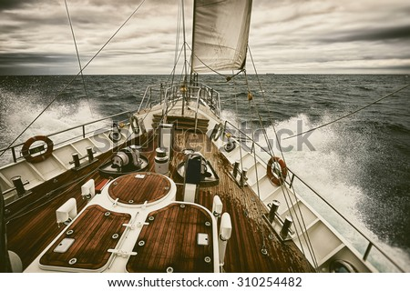 Sailing yacht at sunset during a storm. Toned image and blur. Retro style postcard. Sailing. Yachting. Travel