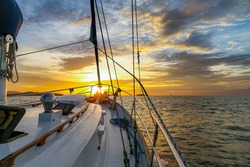 Sailing yacht at sunset in high seas. White hull of a cruise yacht against the backdrop of a calm ocean,  dramatic sky, clouds. Charter bareboat sailboat in the evening. Mast, sail, railing on board