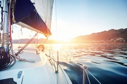 Sailing yacht boat on on ocean water at sunrise with flare and outdoor lifestyle