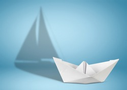 Sailing yacht concept, paper ship with sailing boat shadow on blue