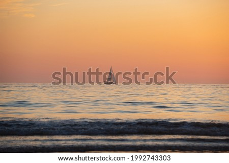 Sailing yacht on sunrise over the sea and beautiful cloudscape. Colorful ocean beach sunset.