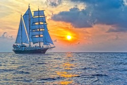 Sailing yacht on the background of a beautiful sunset in the sea
