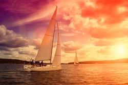 Sailing yacht race, regatta. Sailboat on the background of a beautiful sunset.