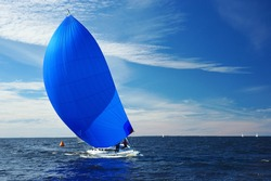 Sailing yacht race. Yachting. Boat with big blue spinnaker sail.