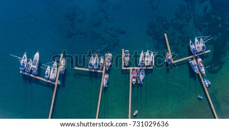 Sailing yachts and boats moored to the wooden piers. Top view.