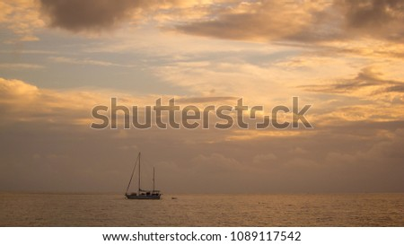 sailingboat in the evening sun on the sea, beautiful clouds and calm colors