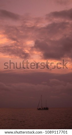 sailingboat in the evening with pink sky on the sea, beautiful clouds and calm colors