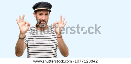 Sailor captain man smoking a tobacco pipe doing ok sign gesture with both hands expressing meditation and relaxation isolated over blue background #1077123842
