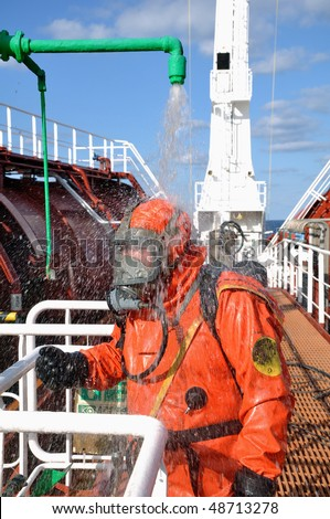 sailor in a protective suit washes himself in the safety shower after  cleaning operations in the cargo tank on a chemical tanker
