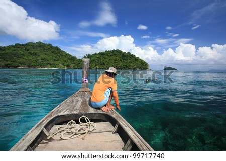 Sailor on wooden boat waiting visitors snorkeling to see coral reef on blue andaman sea at Surin islands national park, Thailand
