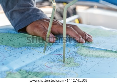 Sailor with divider in front of navigation chart of coastal area. Captain navigating sail boat ship #1442741108