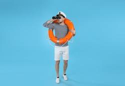 Sailor with orange ring buoy looking through binoculars on light blue background