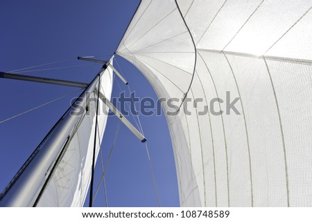 Sails and mast over blue sky background - stock photo