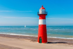 Sailship passing the Lighthouse in Westkapelle, Zeeland province, Netherlands. Westkapelle is a small city with about 2,600 inhabitants. The 16 meter tall cast iron lighthouse was built in 1875.