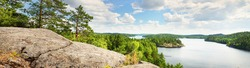 Saimaa lake in a fog at sunrise, Finland, aerial view. Evergreen forest, rocky shores. Picturesque panoramic scenery