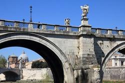 Saint Angel Bridge (Ponte Sant Angelo) in Rome, Italy. Landmark of Rome. Vatican Basilica visible under bridge arch.