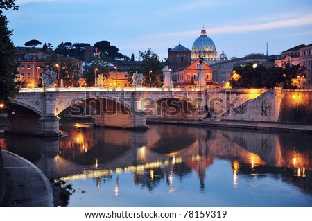 Saint Angelo Bridge and Basilica of St. Peter water reflection in the Tiber river at night with the Vatican city in the background in Rome, Italy