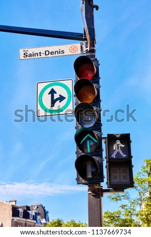 Saint Denis street sign attached to a traffic light signaling green for pedestrian walk in Montreal Quebec Canada #1137669734