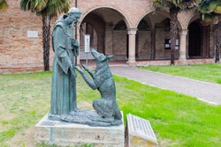 Saint Francis and the wolf statue in front of the XV century gothic roman church dedicated to Saint Francis in Cotignola near Ravenna in the countryside of Emilia Romagna in Italy.