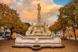 Saint Georg fountain (Sankt Georgsbrunnen) in Gartenfeld district of Trier. It is one of the most beautiful rococo fountains in Germany. Autumn scenery at the morning. Picturesque burning sky