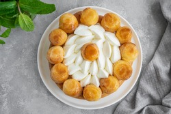Saint Honore cake with profitrols, caramel, custard and whipped cream on a white plate on a gray concrete background. Traditional French dessert. Copy space
