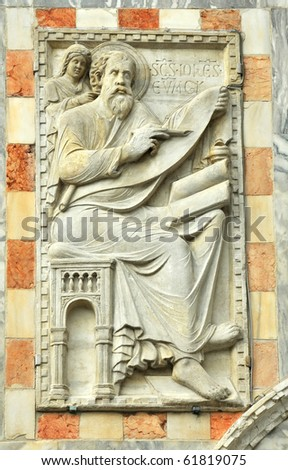 Saint John the evangelist depicted with his gospel receiving divine inspiration. On the facade of the basilica of St Mark's in Venice