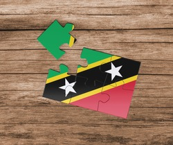 Saint Kitts And Nevis national flag on jigsaw puzzle. One piece is missing. Danger concept.