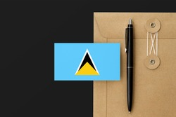 Saint Lucia flag on craft envelope letter and black pen background. National invitation concept. Invitation for education theme.