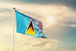 Saint Lucia national flag cloth fabric waving on the sky with beautiful sun light - Image