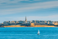 Saint-Malo, Brittany, France: Panoramic view of the walled old town, Intra-Muros, with a solitary sailing boat in the foreground from Dinard, a popular and prestigious seaside resort nearby.
