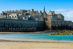 Saint-Malo, Brittany, France: View of the historic fortified part of town (Intra-Muros) from the Sillon beach on a sunny morning at low tide.