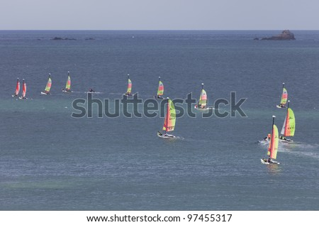 SAINT-MALO, FRANCE - JULY 6: Group of teenagers learning catamaran sailing on the coast of Saint-Malo, France on July 6, 2011. Their Hobie Cat Teddy catamarans are 13 ft long and have a great buoyancy