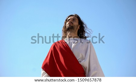 Saint man in robe turns to God, mentally asking for help and forgiving sins