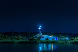 Saint Mary and Jesus Statue with a Cross in Poovar Lake, at night. Thiruvananthapuram, Kerala, India.