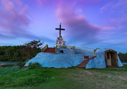 Saint Mary and Jesus Statue with a Cross in Poovar Lake, on a colorful sky background. Thiruvananthapuram, Kerala, India.